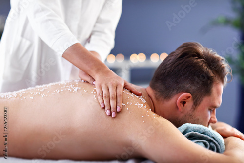 Handsome man having massage in spa salon