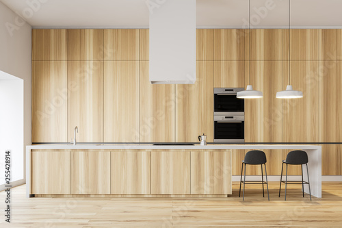 Minimalistic wooden kitchen with bar and ovens - 255428914