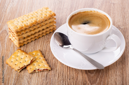 Stack of cookies, cup of coffee, spoon on saucer, broken cookie on wooden table