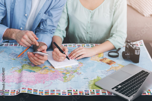 Couple planning vacation trip and writing notes