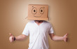 Leinwanddruck Bild - Young man standing and gesturing with a cardboard box on his head with drawn smiley face
