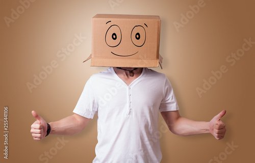 Leinwanddruck Bild Young man standing and gesturing with a cardboard box on his head with drawn smiley face