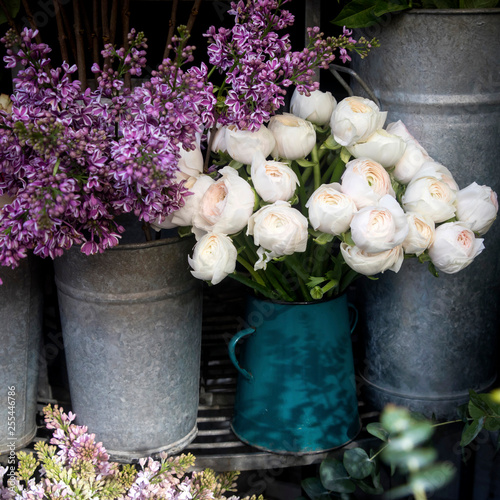 bouquet of lilac and white ranunculus in tin buckets for sale at the entrance to the store