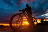 Mountain bike rider silhouette at sunset
