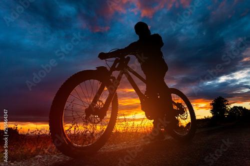 Mountain bike rider silhouette at sunset