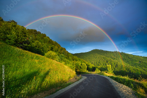 Scenic rainbow landscape on the hills in rural peaceful area © bdavid32