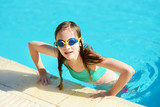 Cute young girl wearing swimming goggles having fun in outdoor pool. Child learning to swim. Kid having fun with water toys.
