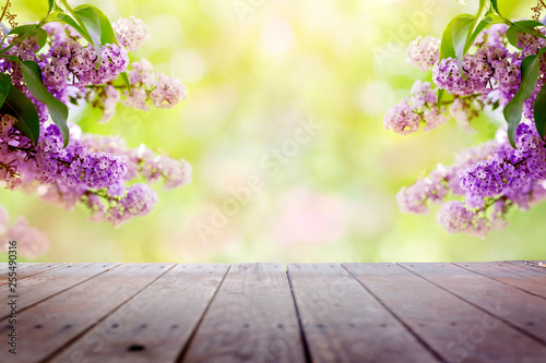 Lilac flowers in the garden over wooden deck background - 255490316