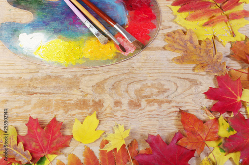 Art palette and brushes on wooden table framed in leaves © yrafoto