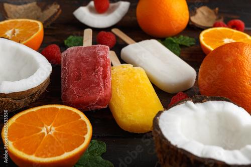 Leinwanddruck Bild Homemade Coconut, Orange, raspberry popsicles, ice lolly, on wooden table. Summer food.