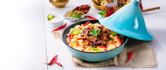 Tajin with couscous, vegetables and meat on white background © Dar1930