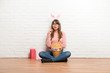 Woman with bunny ears for Easter holidays sitting on the floor standing and thinking an idea - 255546384