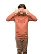 Teenager man with sweatshirt covering eyes by hands. Surprised to see what is ahead over isolated white background