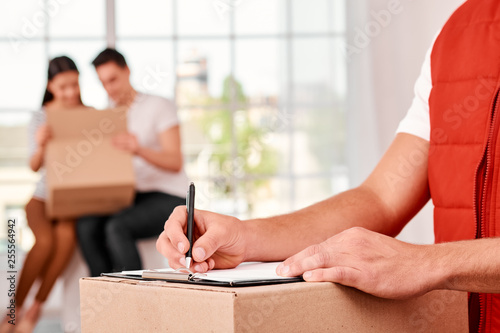 Leinwanddruck Bild Treat others as you want to be treated. Close-up of a delivery man filling in delivery document