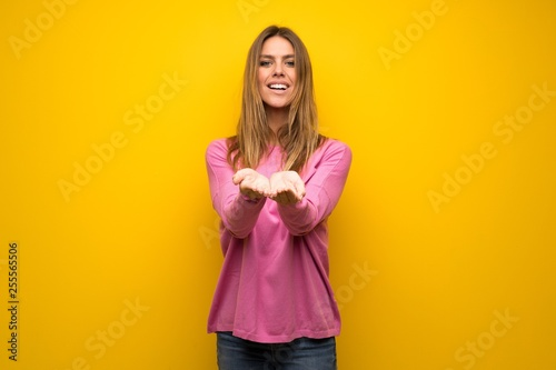 Woman with pink sweater over yellow wall holding copyspace imaginary on the palm to insert an ad
