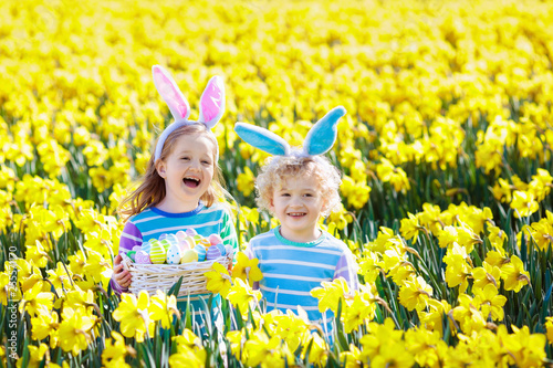 Kids with bunny ears on Easter egg hunt. © famveldman