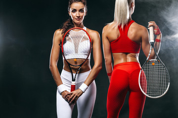 Two women athlete and tennis players on black background. Sport and tennis concept.