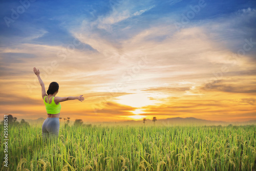 Beautiful woman standing with raised arms on rice field green grass.
