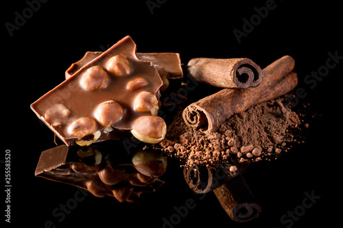 fototapeta na ścianę Pieces of broken chocolate bar, heap of cocoa powder and sticks of cinnamon on black.