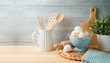 Easter baking background with eggs and kitchen utensils on wooden table