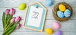 Easter holiday background with easter eggs in bird nest, note and tulip flowers on wooden table.