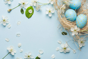 painted blue Easter eggs in the nest on the background of cherry blossoms