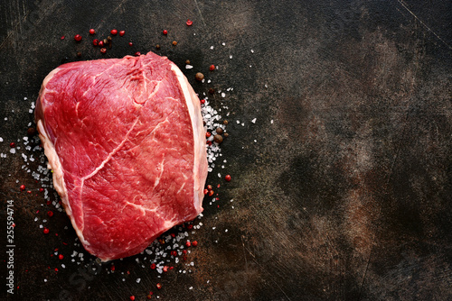 Leinwandbild Motiv Fresh raw marbled beefsteak with spices and salt.Top view with copy space.