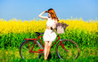 Redhead girl with bike and flowers in basket