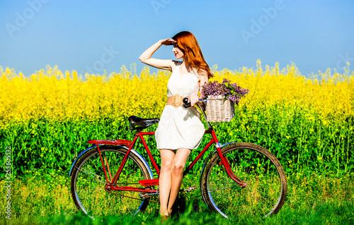 Redhead girl with bike and flowers in basket © Masson