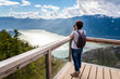 Leinwanddruck Bild - Woman Hiker Taking Photos from a Viewing Deck on the Top of a Mountain. Impressive Panorama. Squamish, BC, Canada.