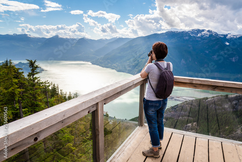 Leinwanddruck Bild Woman Hiker Taking Photos from a Viewing Deck on the Top of a Mountain. Impressive Panorama. Squamish, BC, Canada.