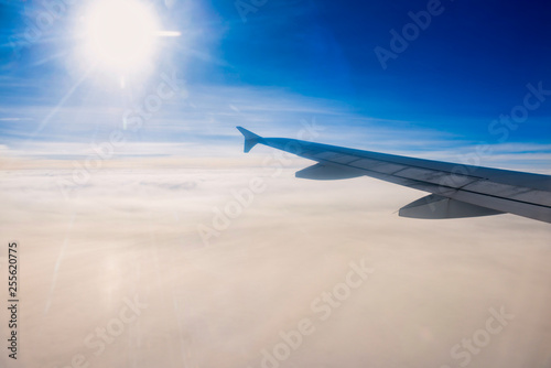 Cloudscape view with horizon line, bright sun and airplane wing - 255620775