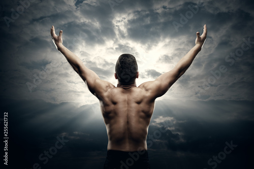 Leinwandbild Motiv Athletic Man Open Arms on Sunrise Sky, Muscular Athlete Body Back Rear View over Sunset Background
