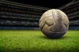 Fototapeta Fototapety sport - Vintage football ball on the grass field in stadium © Rumir