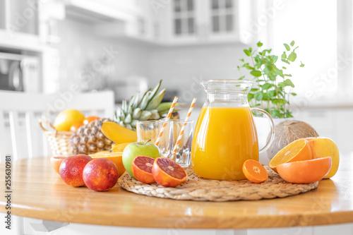 Multifruit juice and fresh fruit on table on kitchen background closeup