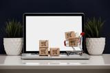 papierowe pudełka w koszyku na klawiaturze laptopa. Koncepcje zakupów online, które konsumenci mogą kupować bezpośrednio z domu lub biura, korzystając z kilku kliknięć w przeglądarce internetowej.