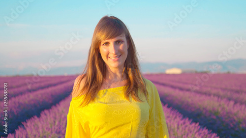CLOSE UP: Smiling young woman walking through purple lavender field - 255638781