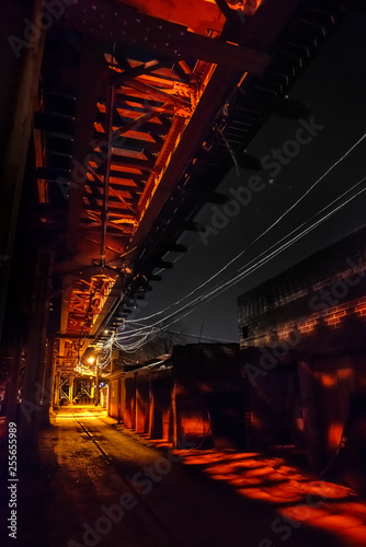 Scary urban city alley with elevated illuminated vintage railway tracks at night in Chicago