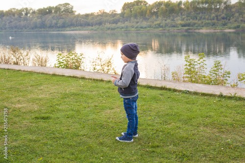 Children and childhood concept - young boy walking near the river