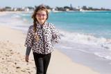 Bimba che passeggia sulla spiaggia sorridendo