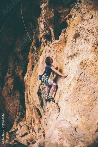 A girl climbs a rock.