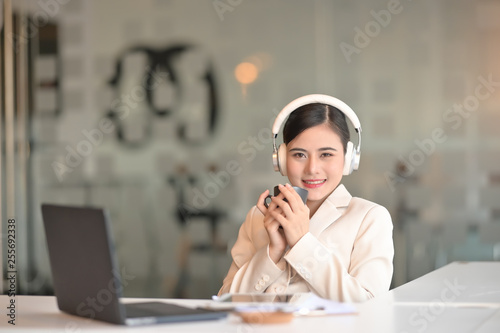 Businesswoman holding a coffee cup and listening a music relax feeling.