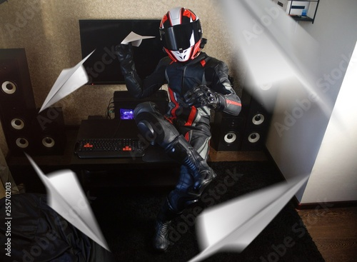 Beautiful motorcyclist in full gear and helmet launches paper airplane