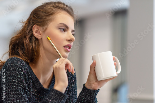 Foto Murales Thoughtful young woman making notes using notepad in kitchen.