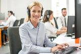 Smiling customer support worker woman with headset working on computer in call center - 255735757