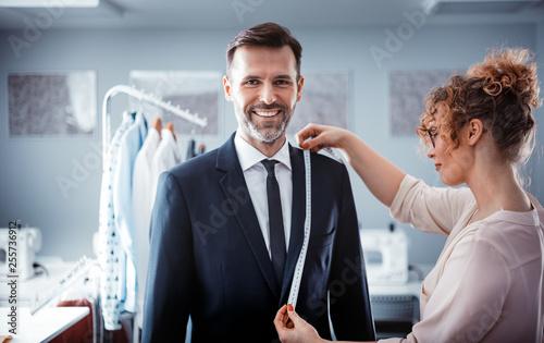 Leinwandbild Motiv Professional tailor using tape to measuring client for sewing suit at fashion design studio