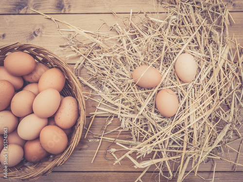 Close up top view of a basket of fresh Italian eggs with hay on the wooden table in the countryside
