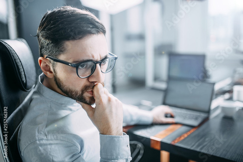 pensive bearded man with glasses on the workplace in the office reflects. The concept of a difficult task at work