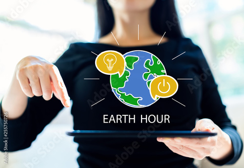 Earth hour with woman using her tablet