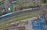Aerial view on blue electric passenger train moving over urban area.